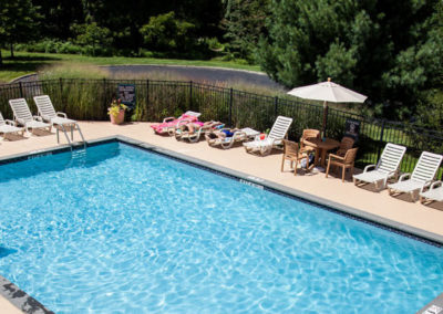 Bethlehem, PA apartments with swimming pool with lounge chairs and umbrellas