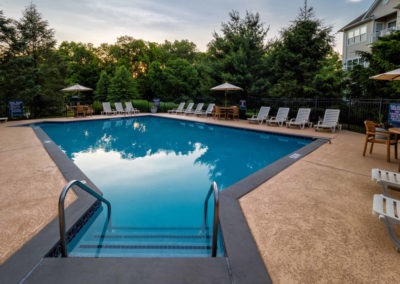 Saucon View apartment community swimming pool with lounge chairs and umbrellas