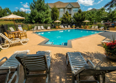 Swimming pool with lounge chairs and umbrellas at Bethlehem, PA apartments