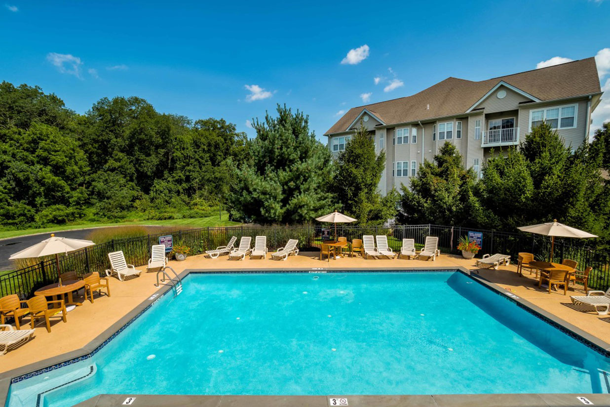 Swimming pool with lounge chairs and umbrellas at Saucon View apartments