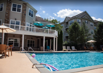 Well-maintained swimming pool and lounging chairs with parasols in Saucon View apartment rentals